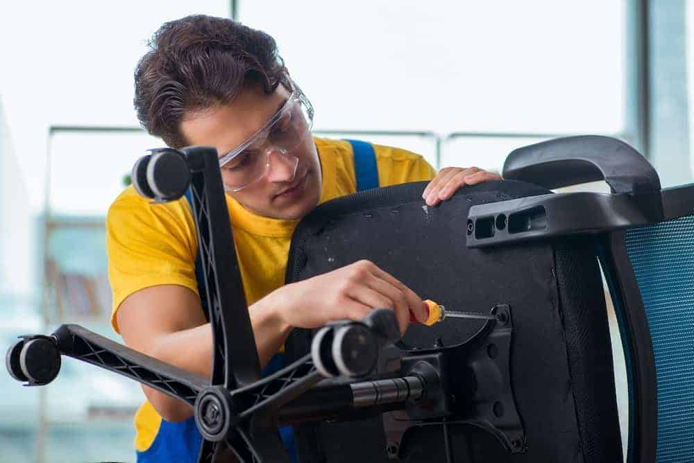 a young technician takes apart a black office chair