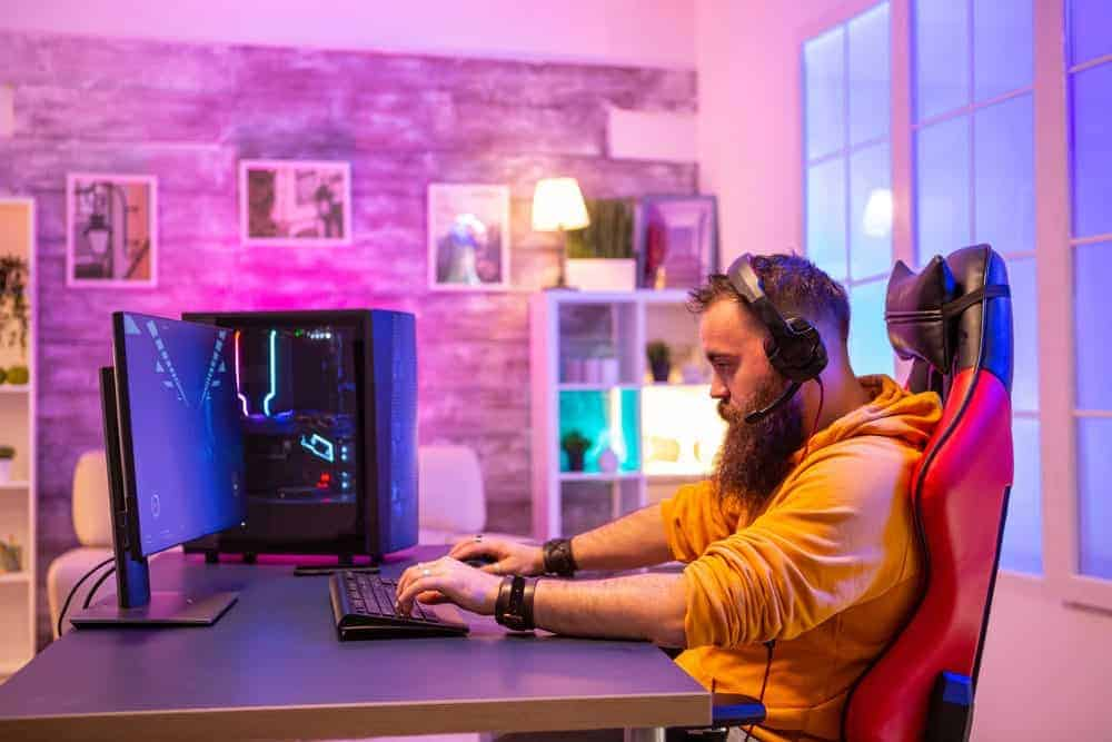 Hipster man sitting in Ficmax gaming chair and playing professional video games in his room