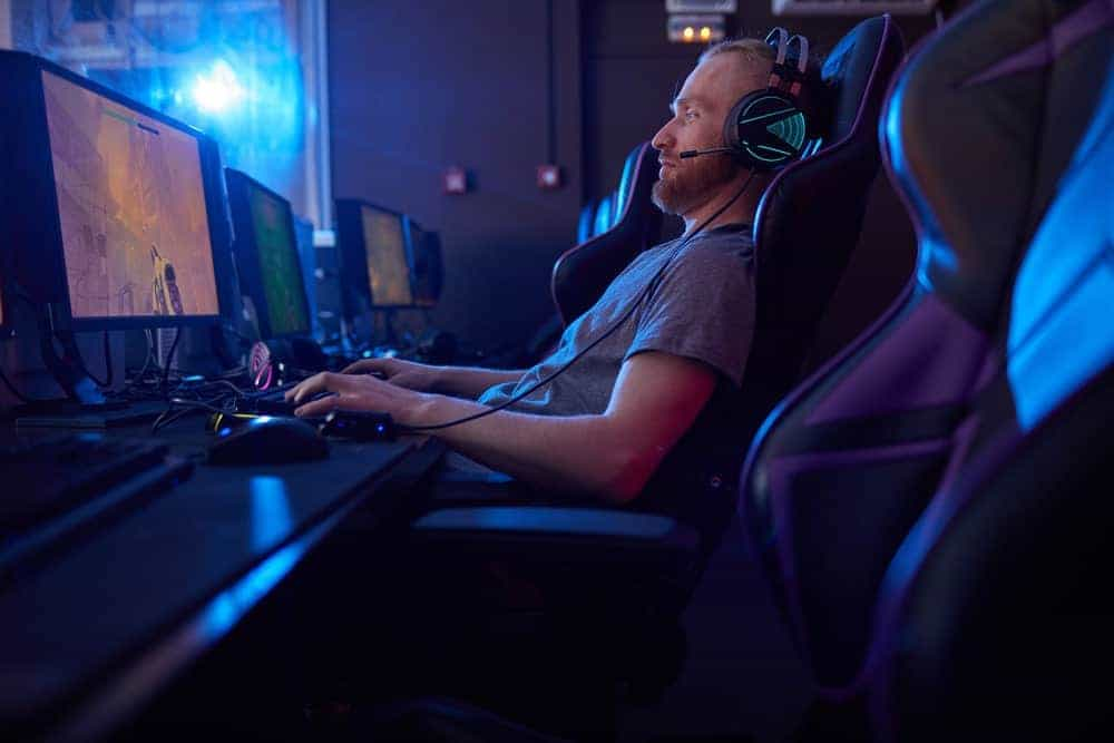 Young bearded man in headphones sitting in Ficmax gaming chair and playing computer game