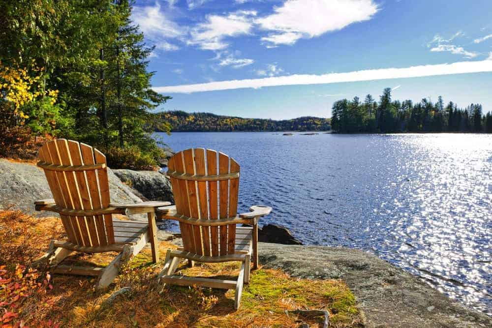two Adirondack chairs at lake shore