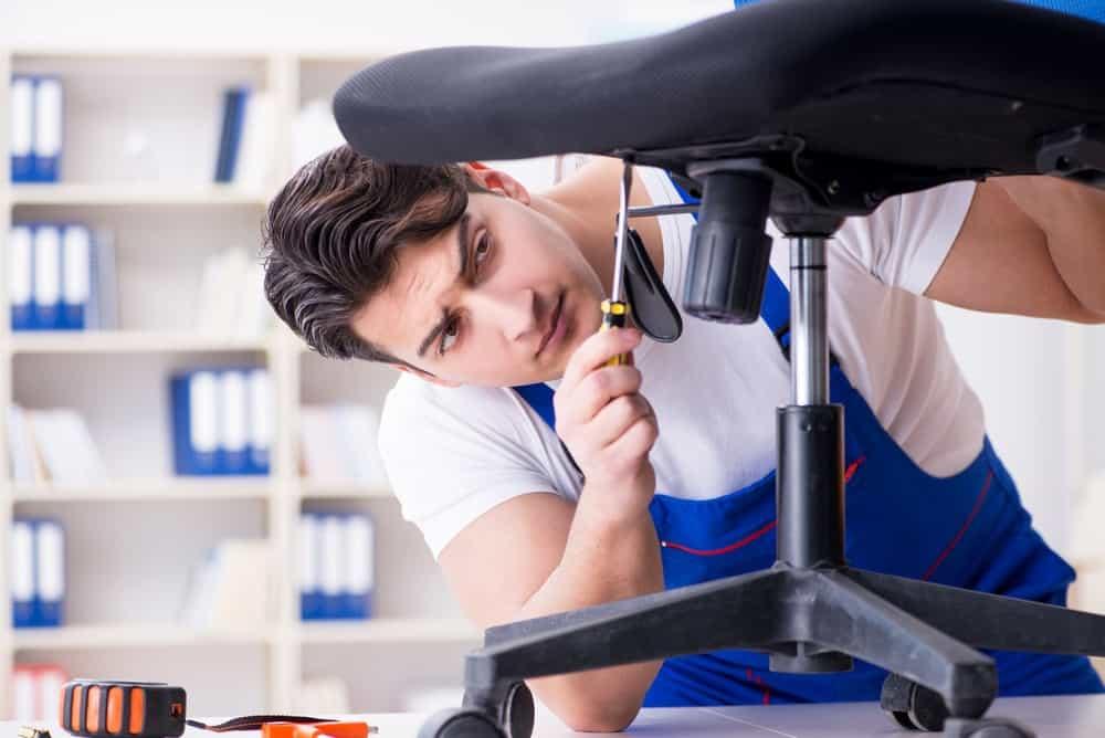 Man Fix An Office Chair That Leans Forward