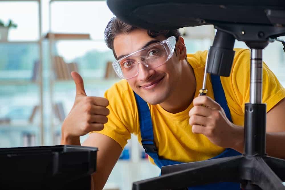 a repairman replacing office chair base