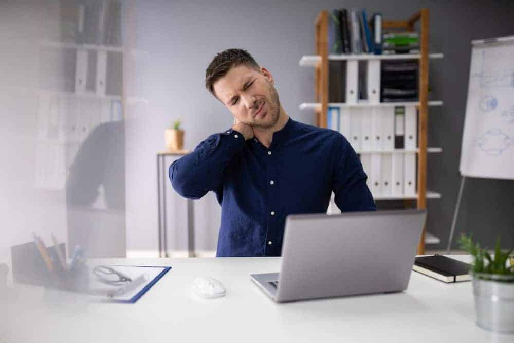 businessman in office chair suffering from neck pain
