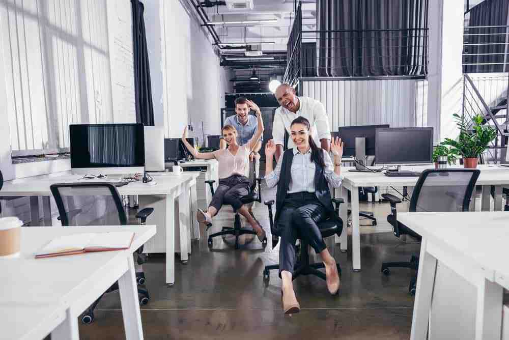group of colleagues having fun in expensive office chairs