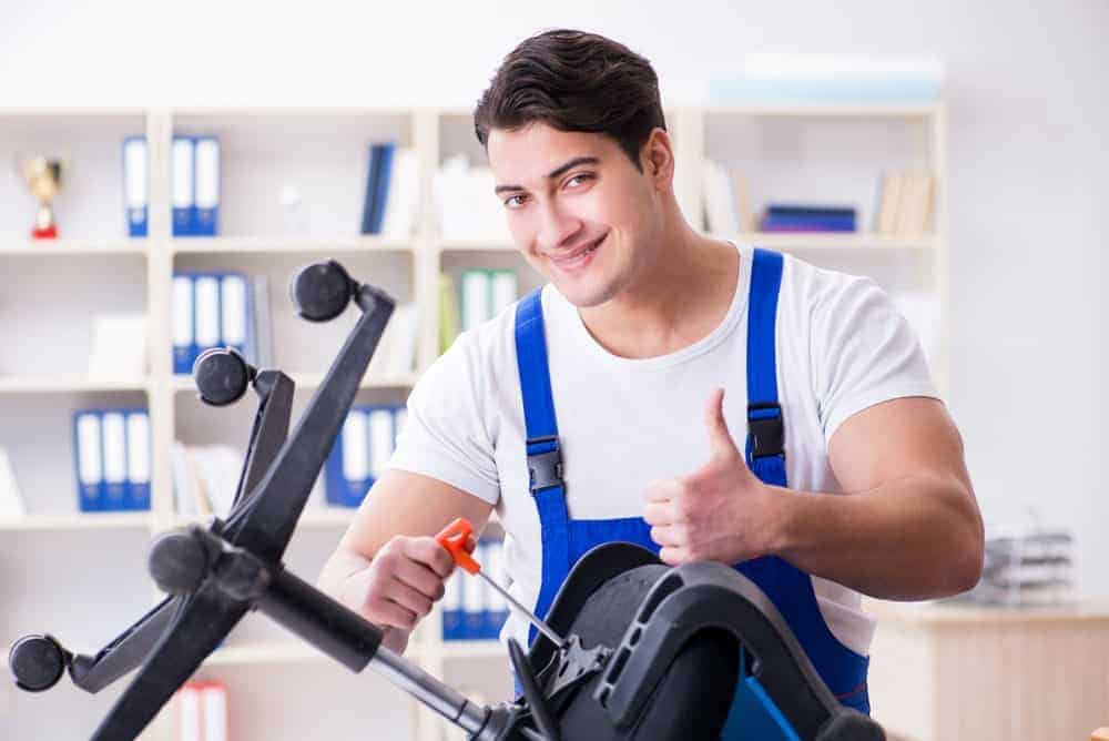 young man fixing office chair