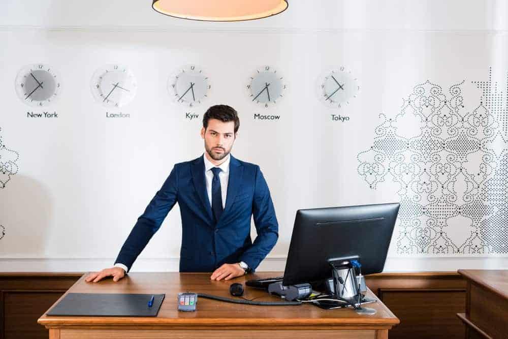 Handsome receptionist standing at reception desk