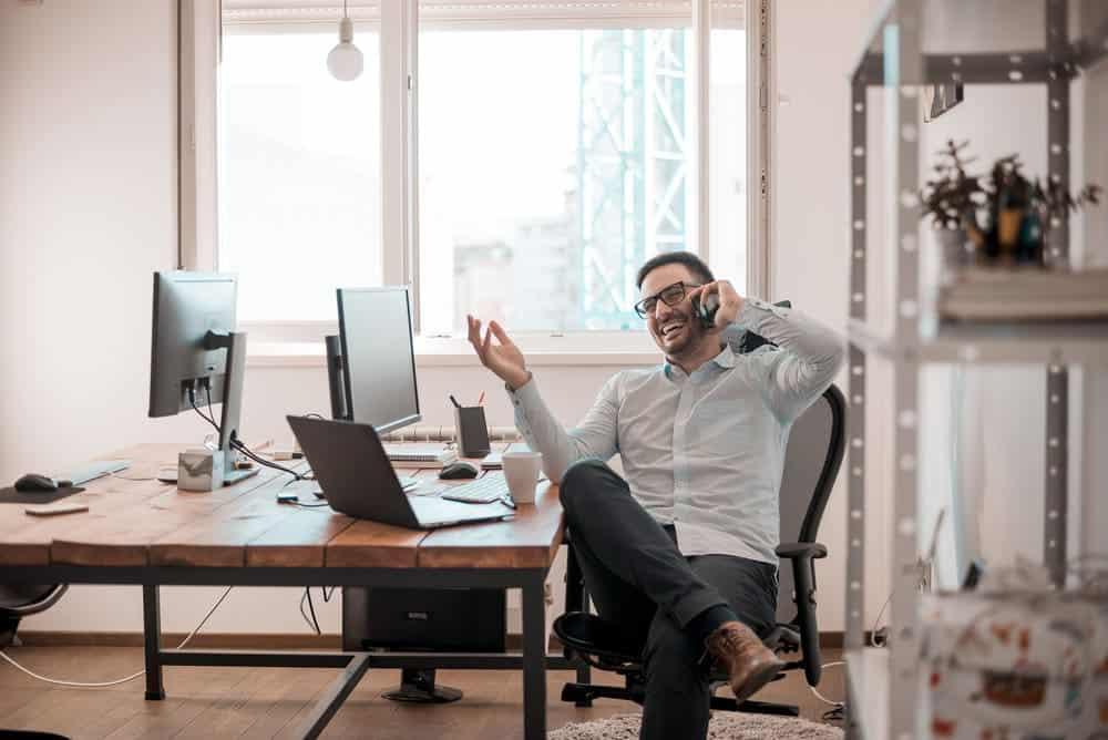 Man in Herman Miller Aeron office chair speaking on mobile phone