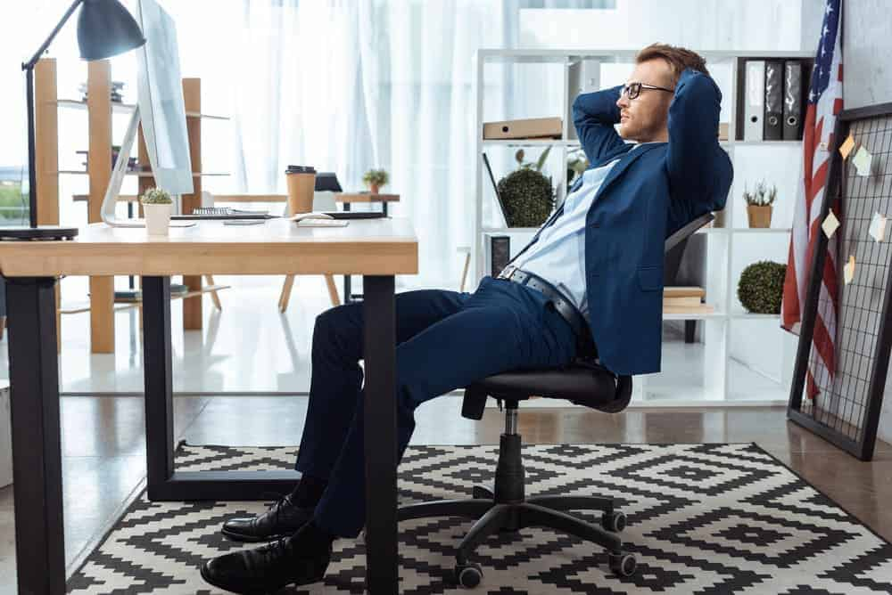 man sitting in a standard office chair