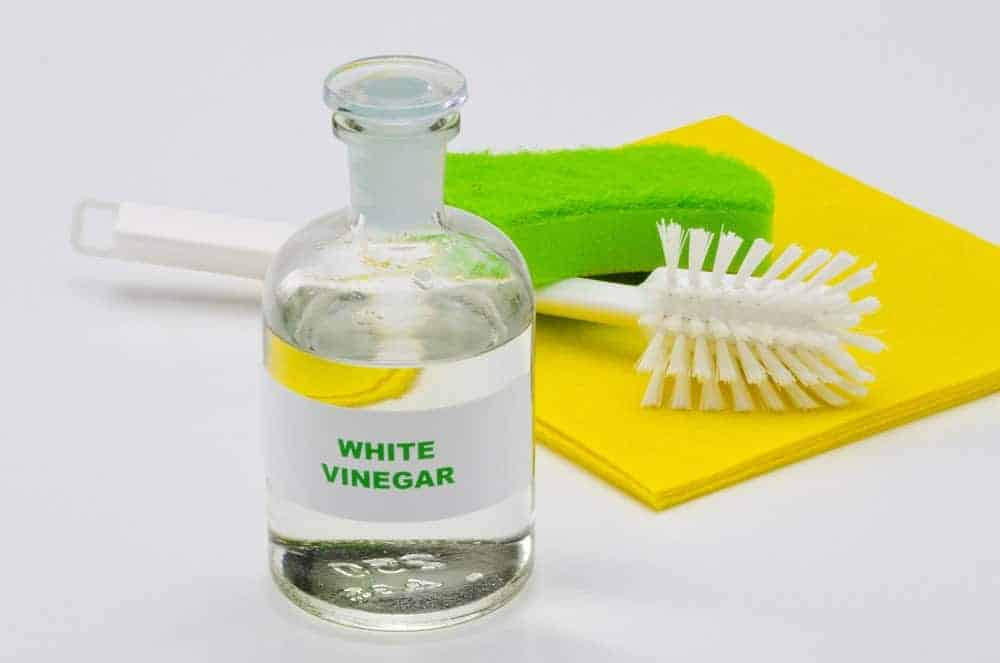 white vinegar, brush and sponge for cleaning leather office chair