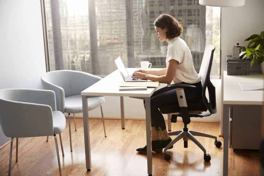woman on steelcase leap office chair working on laptop