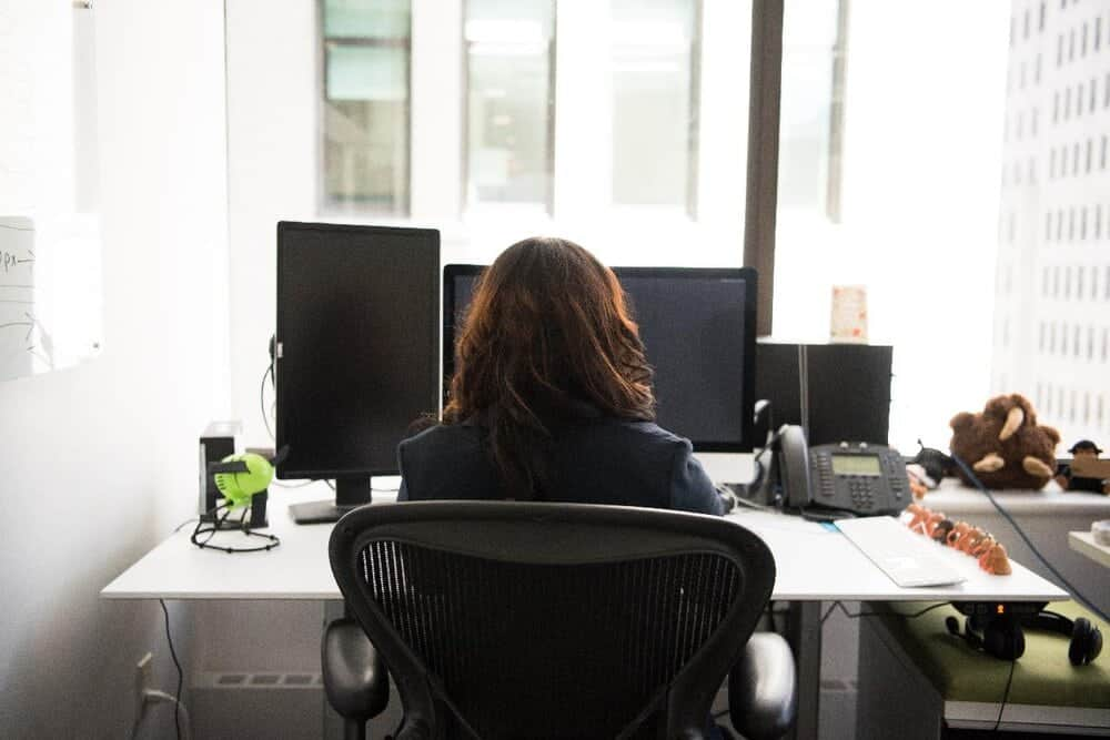 woman sitting in mid back office chair