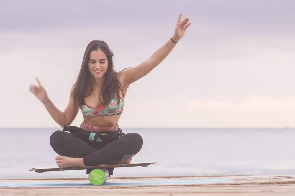 girl sitting cross-legged and keeping balance on a board